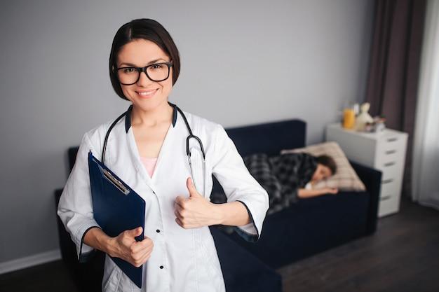 El doctor de sexo femenino joven positivo detiene el pulgar grande. ella sostiene la tableta de plástico en la mano y el estetoscopio alrededor del cuello. niño enfermo acostado en el sofá detrás. ella duerme.