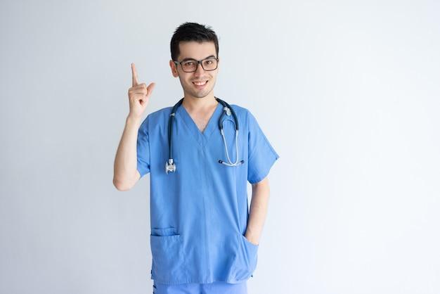 Doctor de sexo masculino joven sonriente que señala hacia arriba