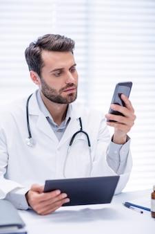 Doctor de sexo masculino que usa el teléfono móvil mientras sostiene la tableta digital