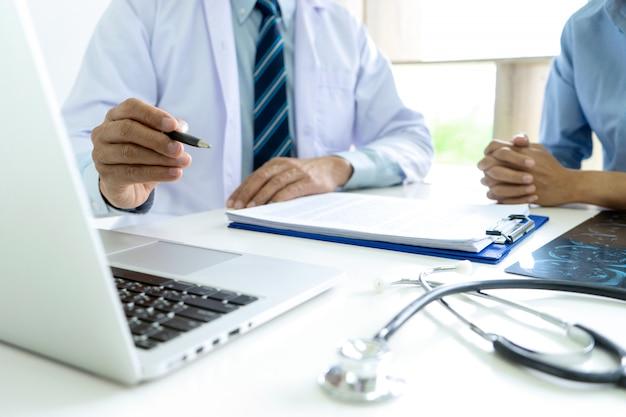El doctor se sienta con el consultor del paciente para hablar sobre salud