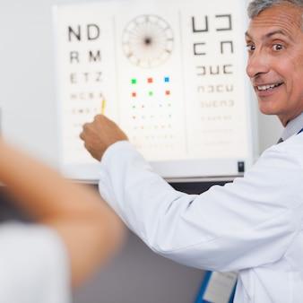 Doctor sonriendo mientras hace una prueba ocular en un paciente en un hospital