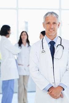 Doctor sonriendo mientras su equipo se comunica en el fondo.