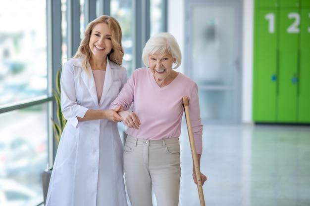Doctor sonriente en una bata de laboratorio caminando con un paciente mayor