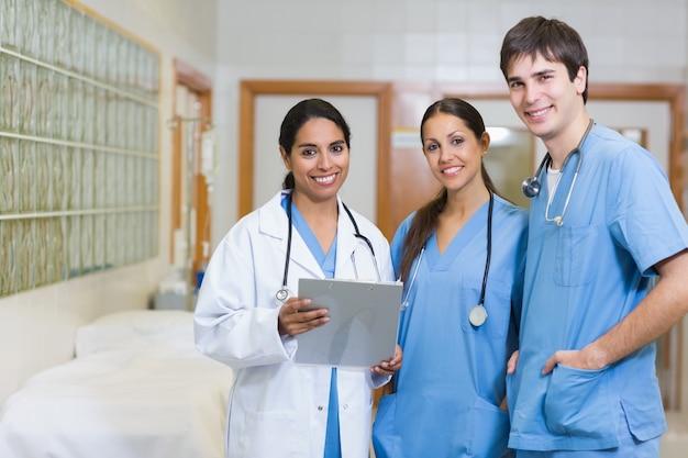 Doctor sonriente y enfermera masculina y femenina sonriente en un pasillo