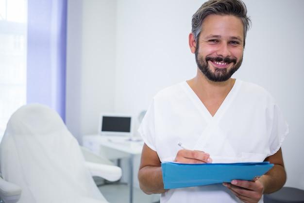 Doctor sonriente escribiendo en informes médicos en clínica