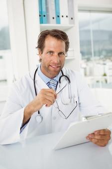 Doctor sonriente con informes en el escritorio médico