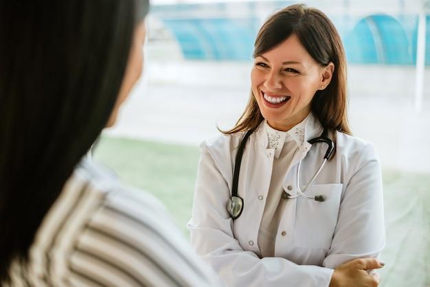 Doctor sonriente joven que habla con el paciente en oficina