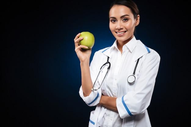 Doctor sonriente joven de la señora que sostiene la manzana y que mira
