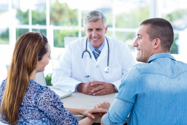 Doctor sonriente mirando feliz pareja en consultorio médico