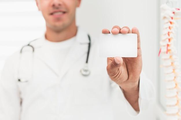 Doctor sonriente mostrando tarjeta simulacro