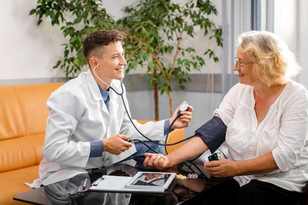 Doctor sonriente que mide la tensión a un paciente