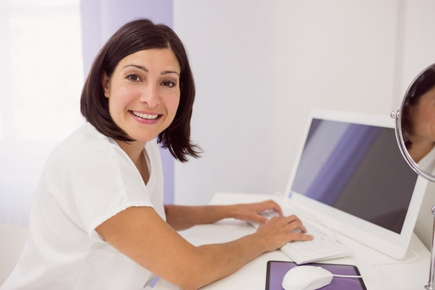 Doctor sonriente que usa la pc de escritorio