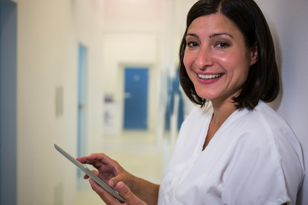 Doctor sonriente que usa la tableta digital en la clínica