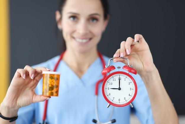 Doctor sonriente tiene reloj despertador rojo y medicación en su mano
