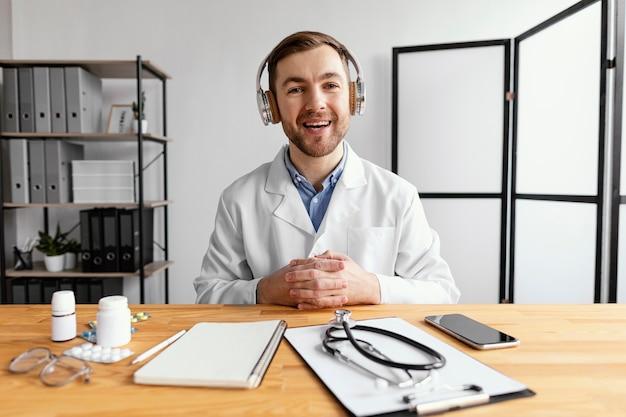 Doctor sonriente de tiro medio en el escritorio