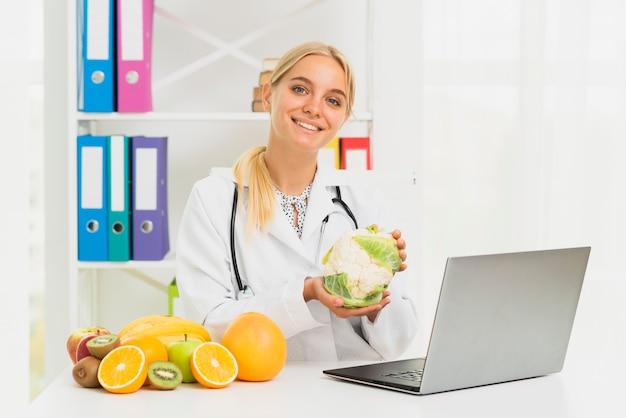 Doctor sonriente de tiro medio con laptop y coliflor