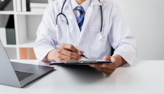 Doctor sosteniendo el archivo de informe del paciente para evaluar los síntomas en el escritorio.