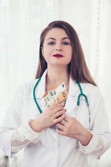 Doctor sosteniendo billetes en euros, medicamentos y sobornos