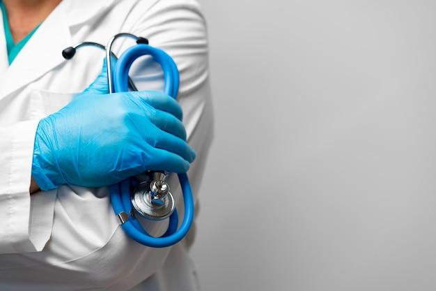 Doctor sosteniendo un estetoscopio con los brazos cruzados con guantes azules cerrar