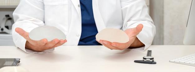 Doctor sosteniendo implantes de silicona para aumento de senos