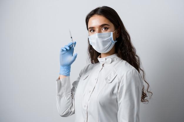 Doctor sosteniendo una jeringa con vacuna contra el coronavirus. chica atractiva en guantes médicos con jeringa y medicación