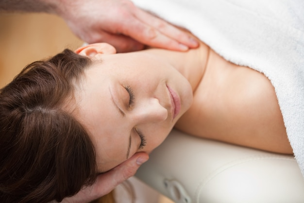 Doctor sosteniendo la cabeza de una mujer mientras masajea su cuello