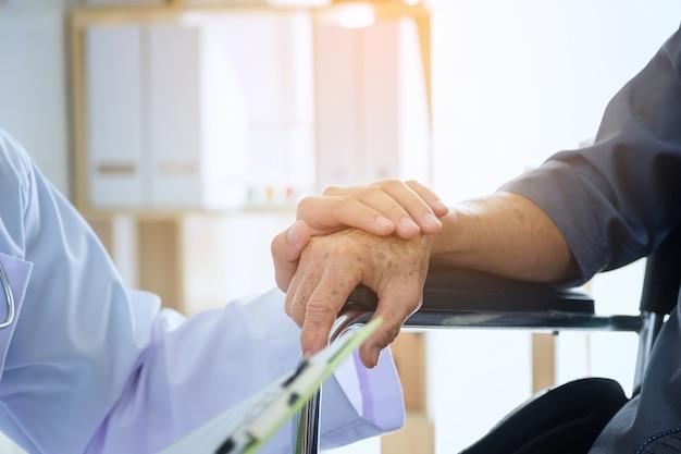 Doctor sosteniendo la mano del paciente anciano en una silla de ruedas