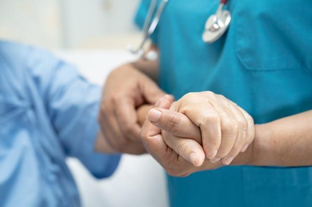 Doctor sosteniendo la mano paciente mujer mayor asiática con amor.