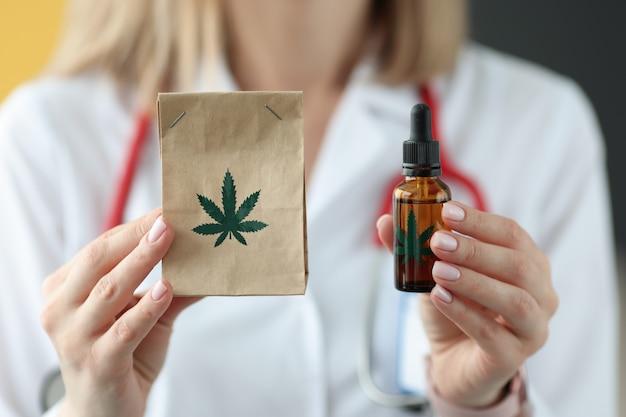 Doctor sosteniendo el paquete de primer plano de marihuana y aceite. concepto de tratamiento de drogas