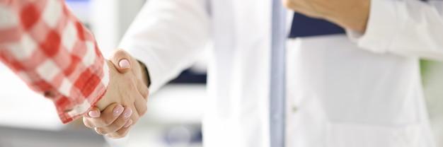 Doctor sosteniendo el portapapeles y estrechar la mano del paciente en la operación de coordinación de primer plano de la clínica