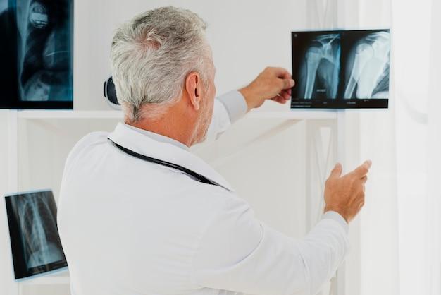 Doctor sosteniendo rayos x contra la luz