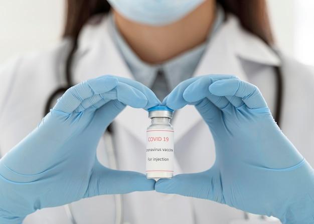 Doctor sosteniendo un recipiente de vacuna