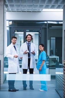 Doctor sosteniendo tableta digital de pie con colegas