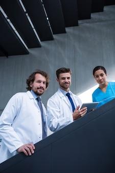 Doctor sosteniendo tableta digital de pie en la escalera con colegas