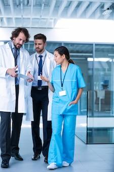 Doctor sosteniendo tableta digital teniendo una discusión con colegas