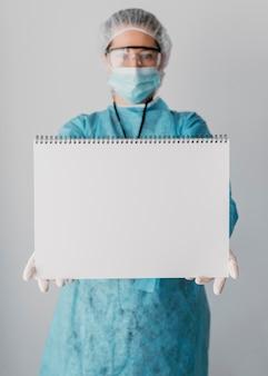 Doctor sosteniendo una tarjeta en blanco