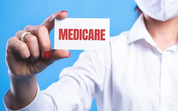 Doctor sosteniendo una tarjeta con el signo de medicare en azul.