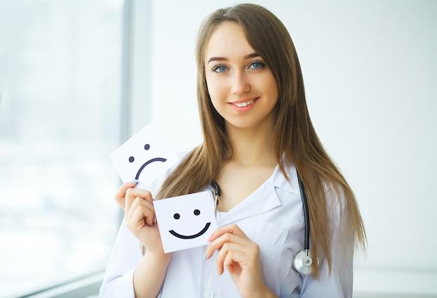 Doctor sosteniendo una tarjeta con el símbolo sonrisa, concepto médico