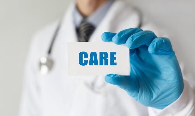 Doctor sosteniendo una tarjeta con texto care, concepto médico