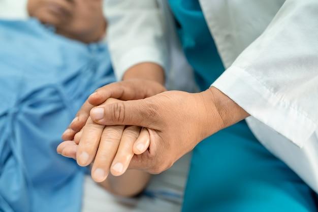 Doctor sosteniendo tocar las manos paciente mujer senior asiática con amor cuidado ayudando a alentar