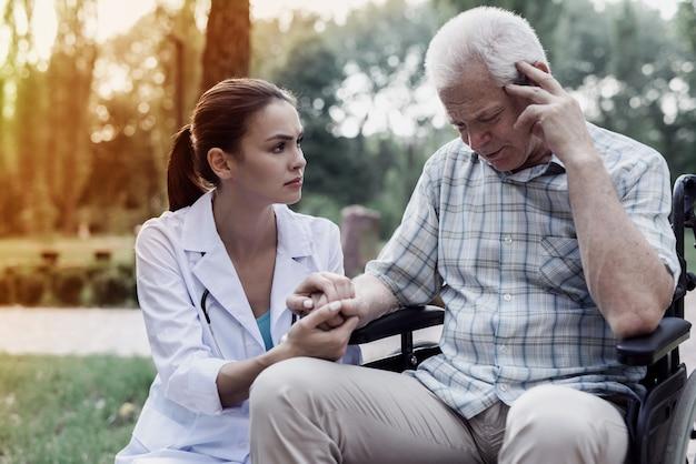 Doctor sosteniendo un viejo mans mano en una silla de ruedas