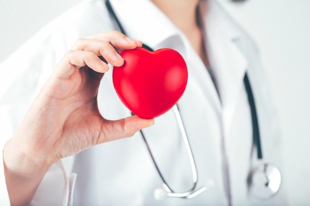 El doctor sostiene y muestra un corazón rojo.