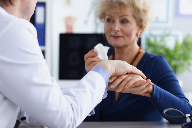 Doctor sostiene con simpatía la mano de un paciente anciano