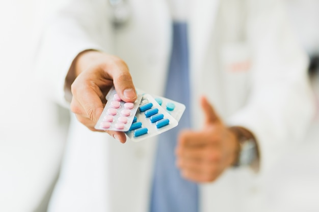 Doctor sujetando pastillas en la mano