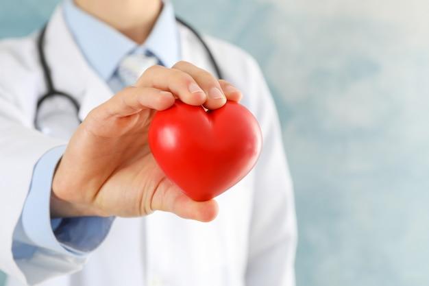 Doctor tiene corazón contra la superficie azul, primer plano