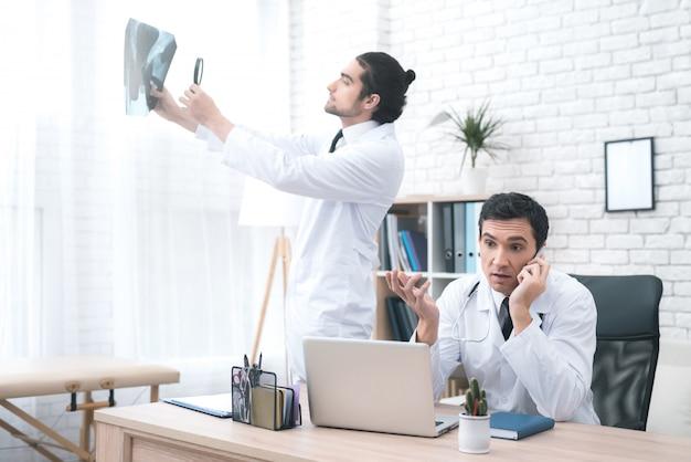 El doctor tiene una llamada telefónica durante la discusión médica.