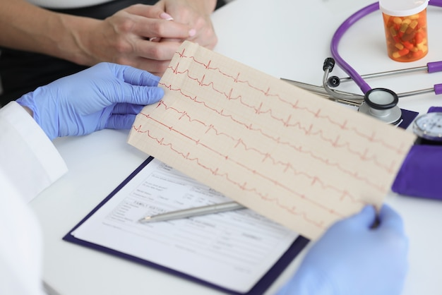 El doctor tiene la transcripción del cardiograma del paciente en sus manos