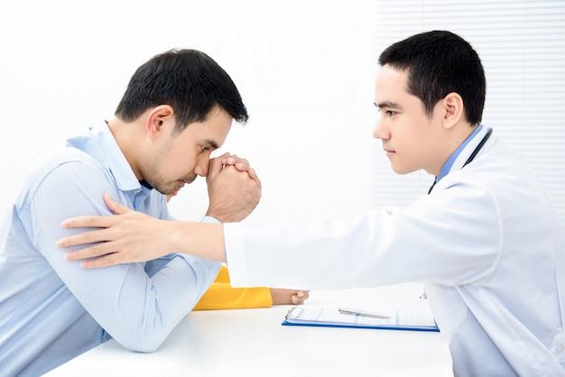 Doctor tocando y consolando paciente masculino deprimido