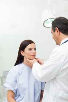 Doctor tocando el cuello de un paciente