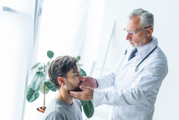 Doctor tocando los ganglios linfáticos del paciente